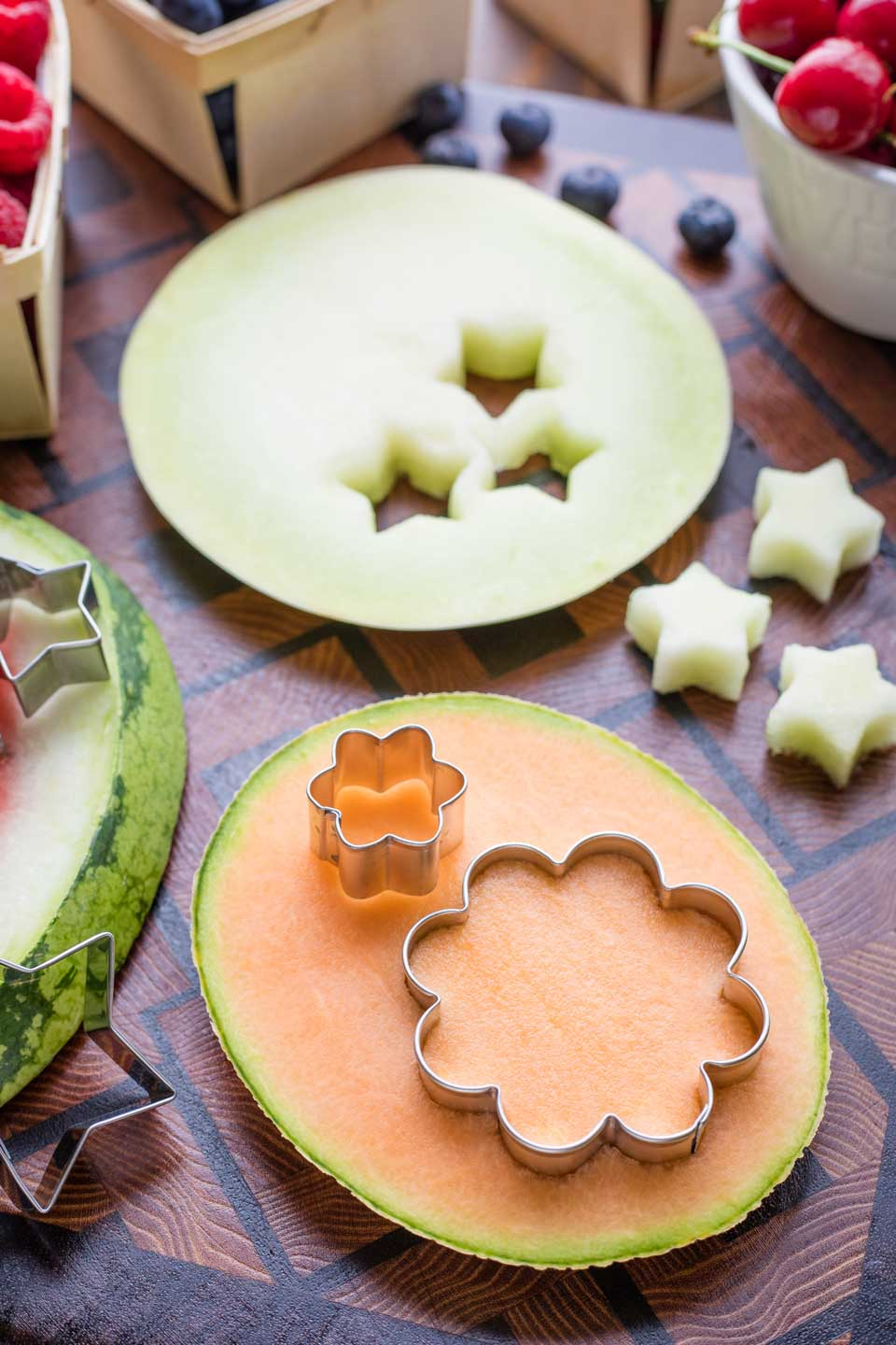 a cantaloupe slice laying flat on a cutting board with flower cutters cutting out shapes, and with other melons and cutters in the background
