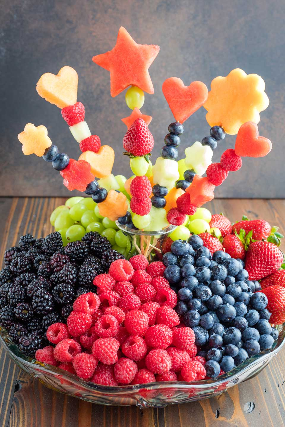 a heaping fruit tray with piles of blackberries, raspberries, blueberries, strawberries and green grapes, and a fruit bouquet at its center