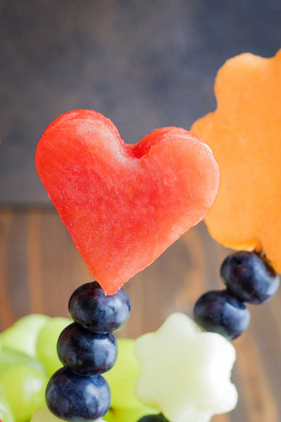 closeup of one kabob out of the bouquet, with a watermelon heart on top and three blueberries underneath