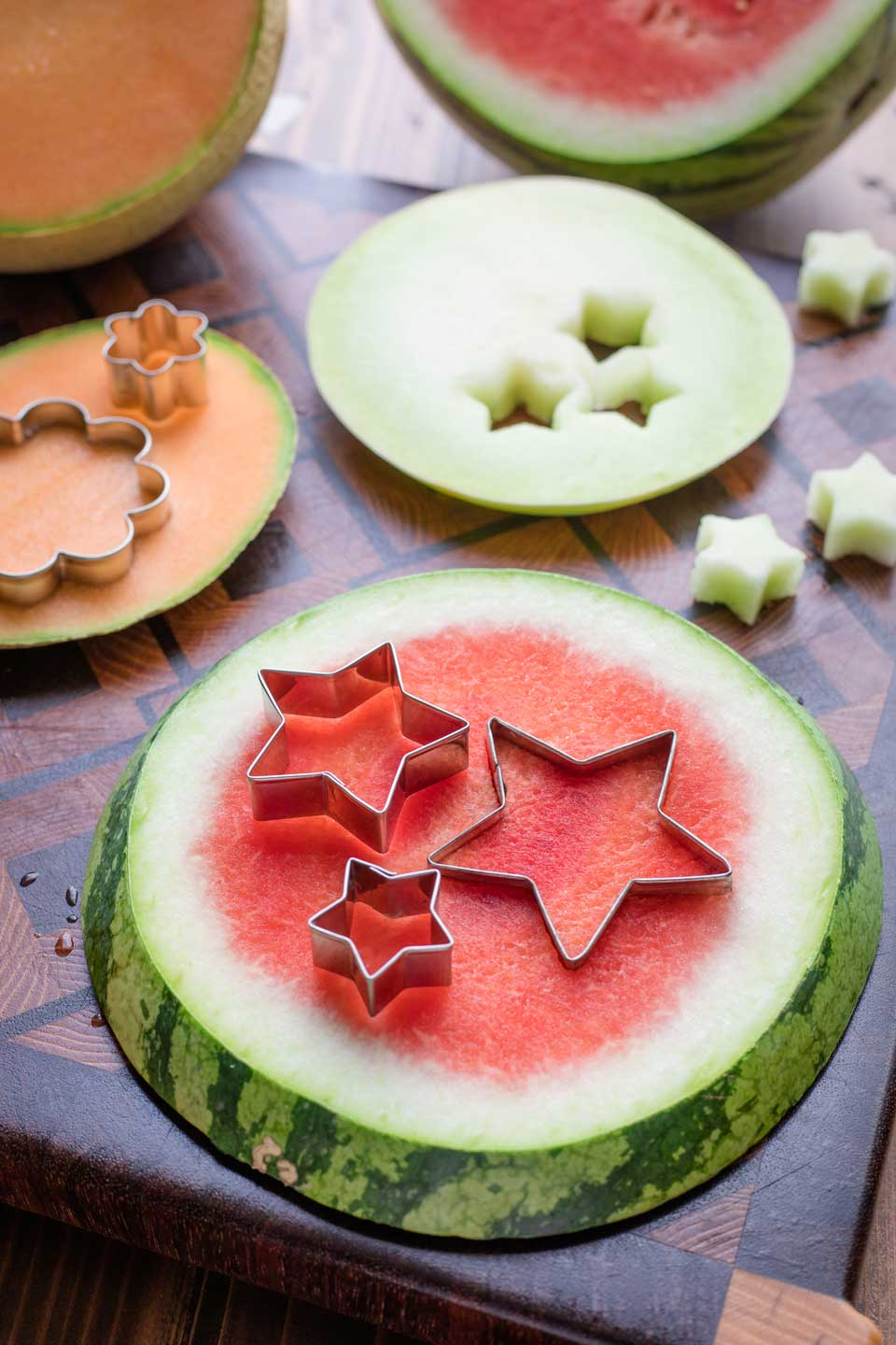 various types of melon laying on a cutting board with different sizes of star-shaped and flower-shaped cookie cutters cutting out shapes from them