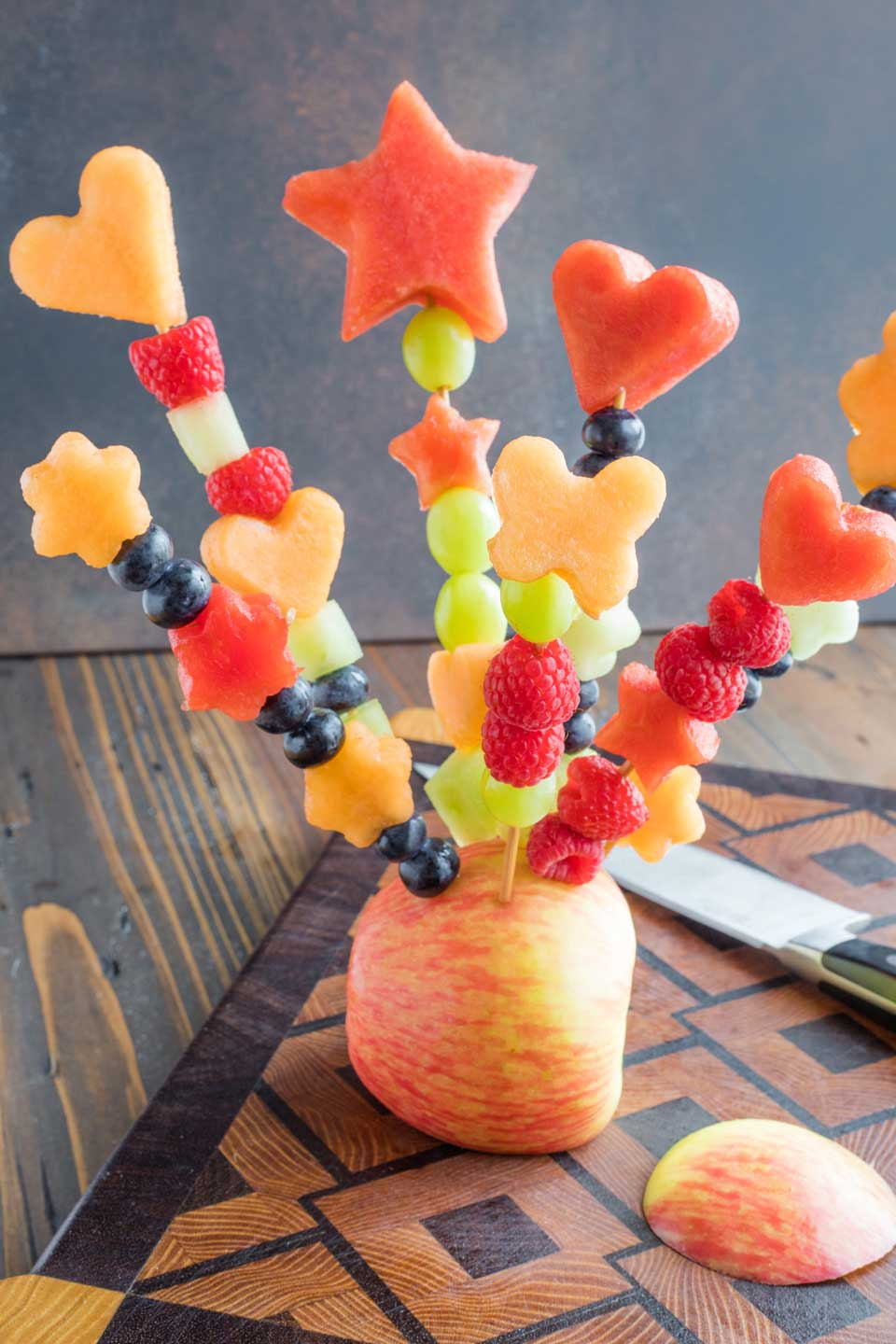 a finished bouquet of fruit flowers, with skewers stuck into an apple base, sitting on a cutting board