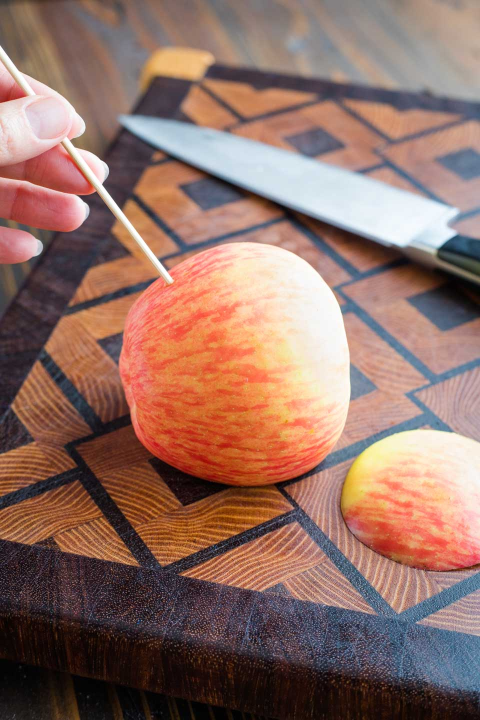 an apple on a cutting board with a slice off one side so it sits flat, and with a hand just starting to poke a skewer in to make a hole in the apple