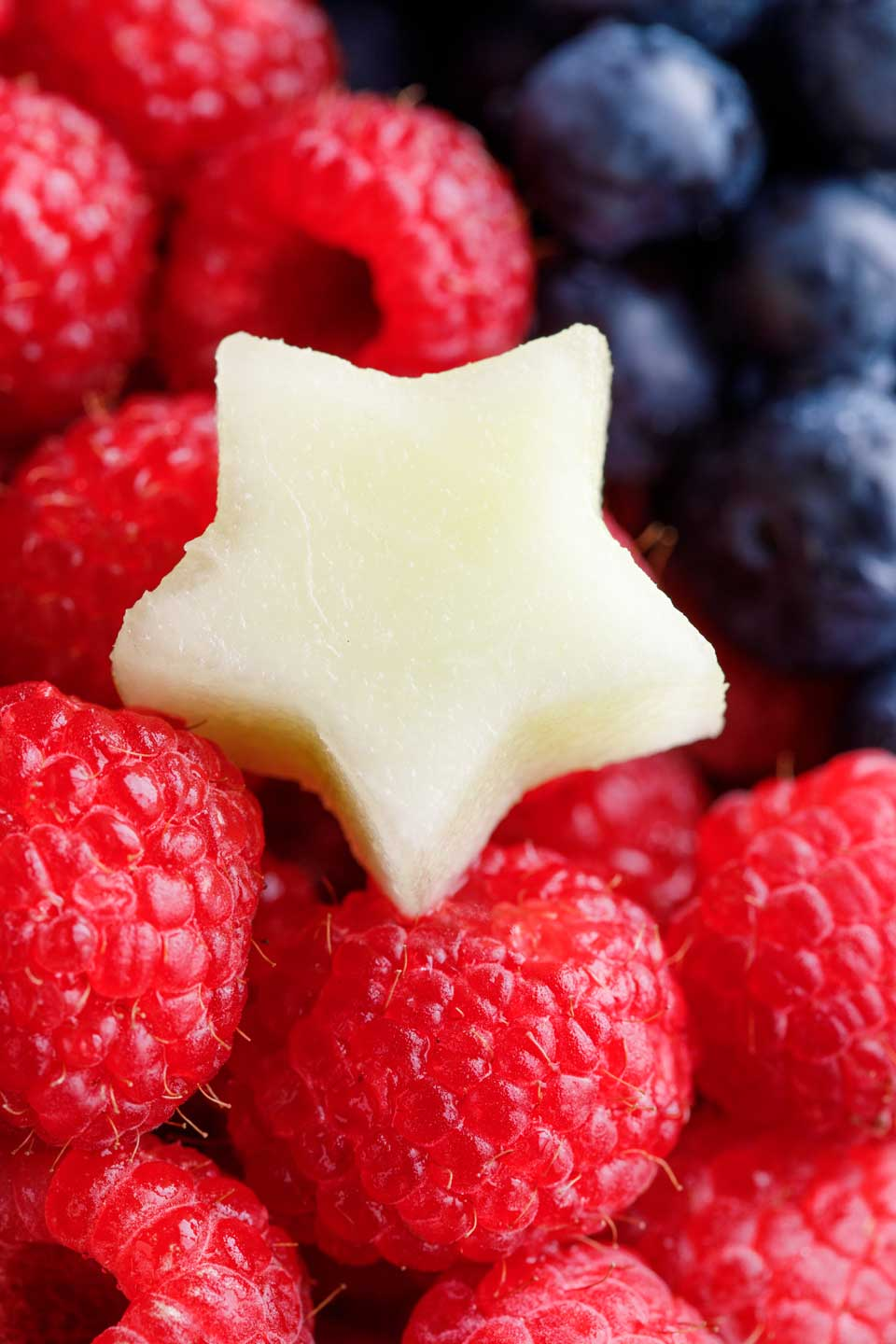 closeup of a little star cut from a honeydew melon, resting on cascades of raspberries and blueberries on a fruit tray