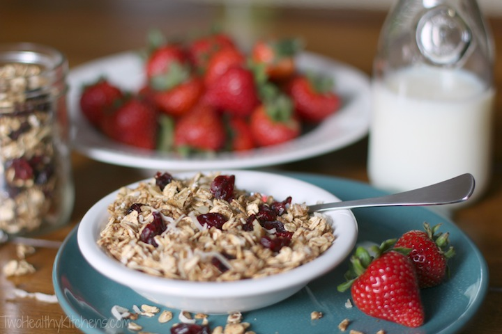 little bowl of granola with a spoon in it, sitting on a turquoise plate and surrounded by strawberries, a small glass jug of milk, and a glass canister of additional granol
