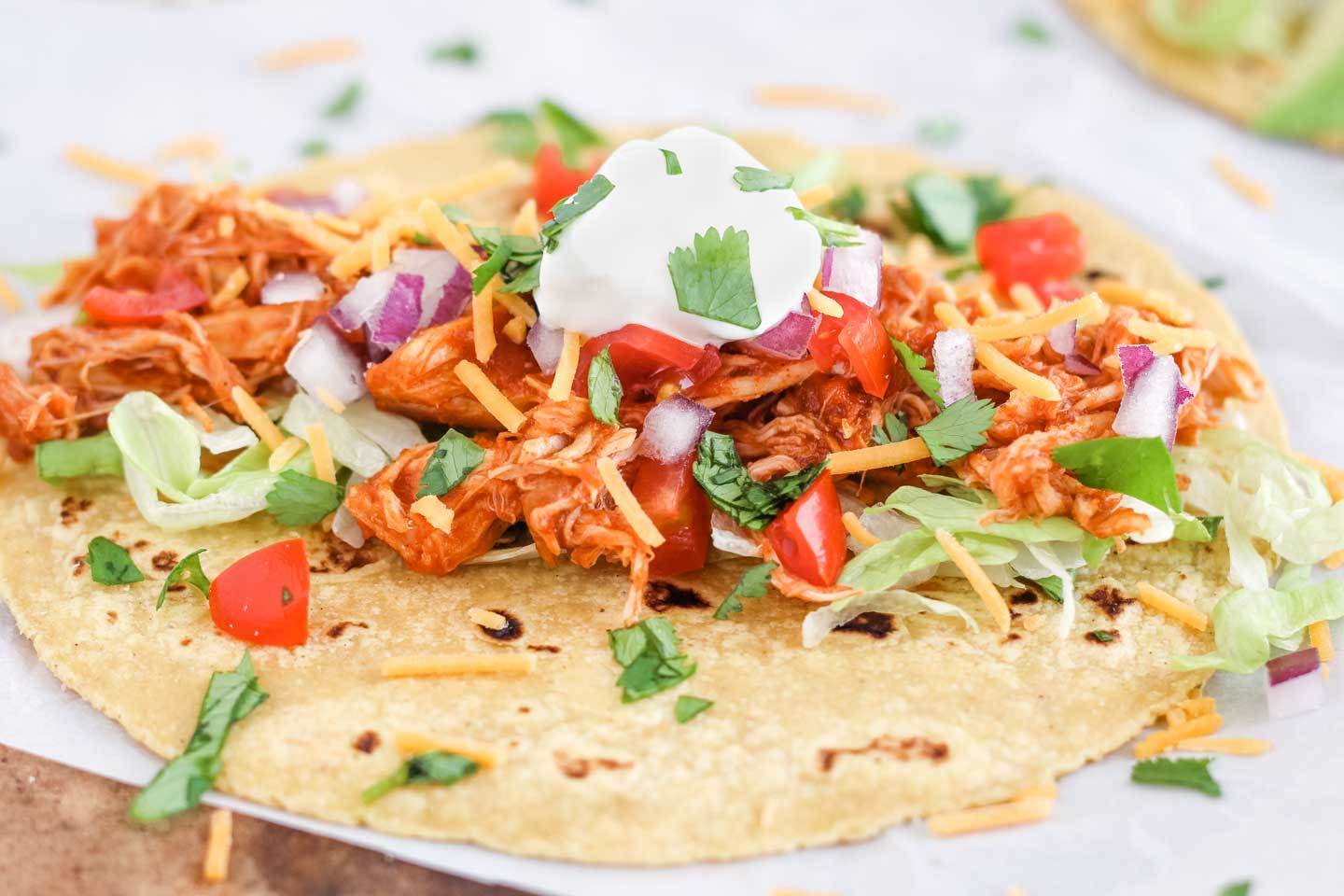 Closeup of one crock pot chicken taco, laid open flat with lots of toppings sprinkled over the chicken, like lettuce, tomatoes, cheese and sour cream.