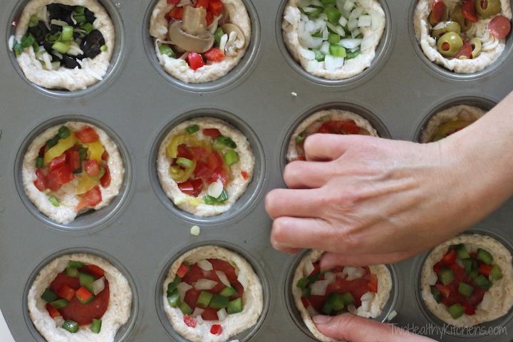 Overhead photo of a muffin tin full of individual, unbaked mini pizzas with all different toppings combinations, and two hands finishing one of the pizzas.