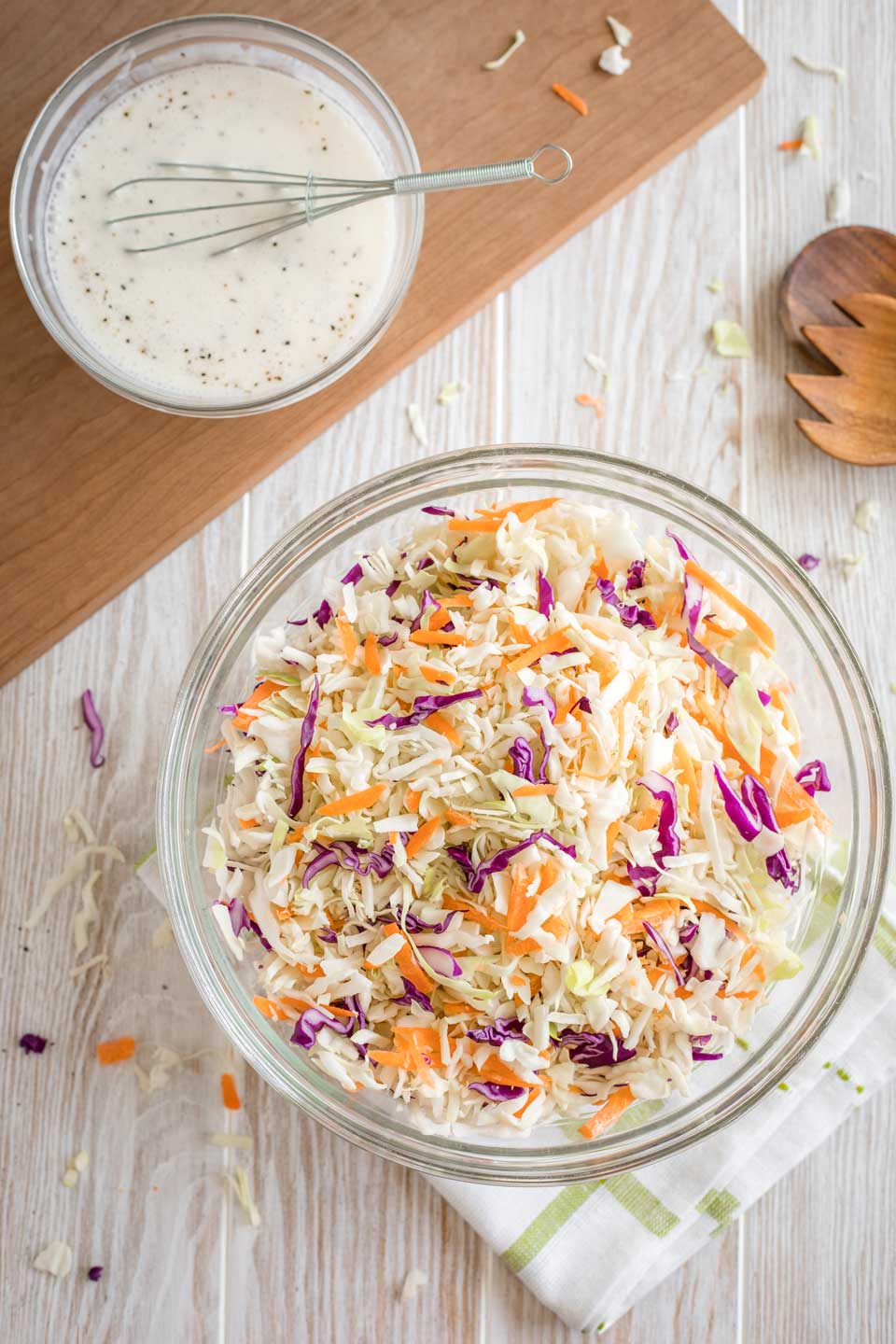 overhead photo of a glass mixing bowl with shredded cabbage in it, with a smaller bowl of the dressing nearby, waiting to be poured over top