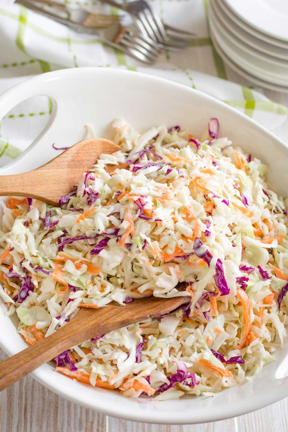 overhead of a white serving bowl of this coleslaw, with two wooden servers scooping in to serve some up