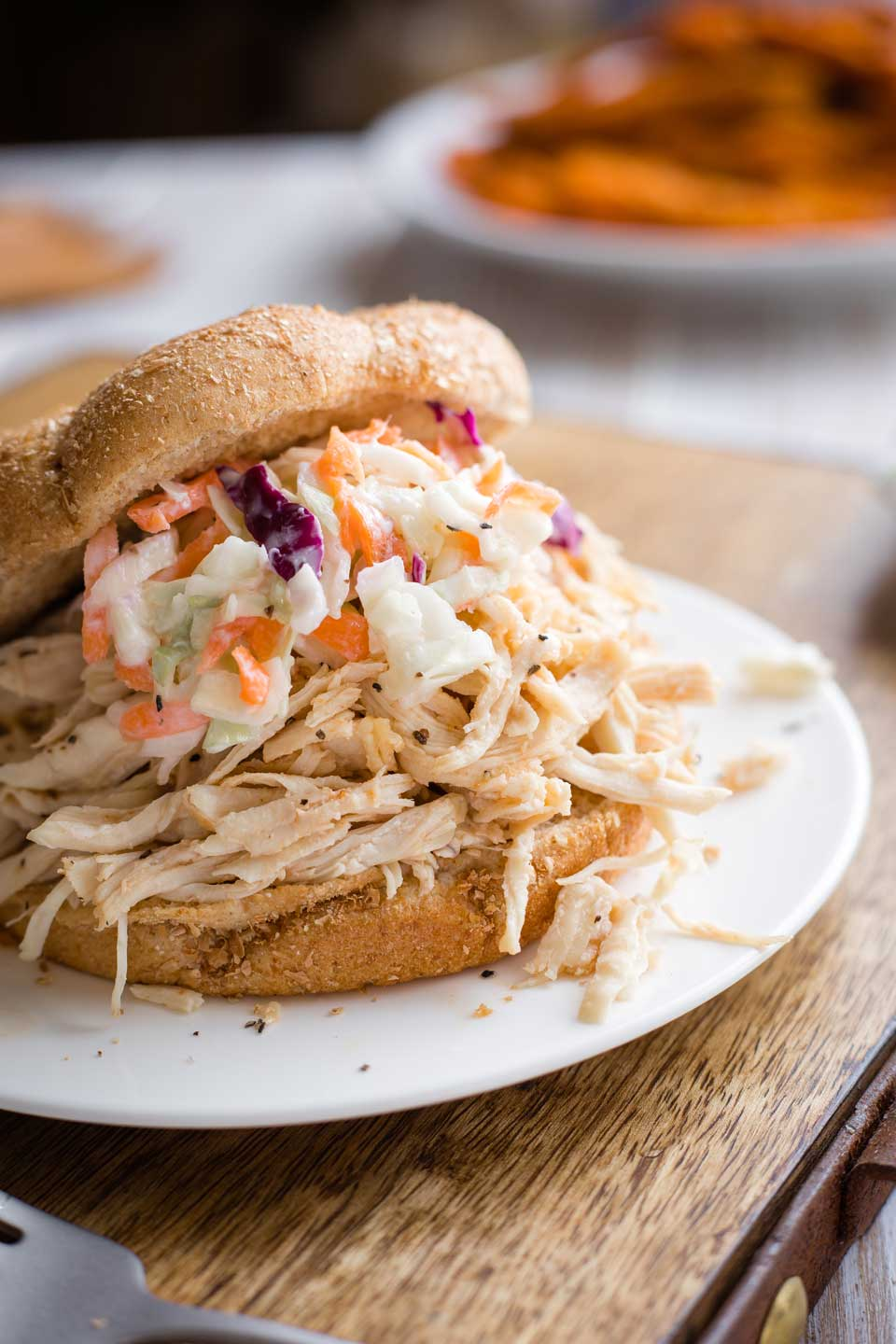a BBQ pulled chicken sandwich on a white plate, with this coleslaw recipe as a sandwich topping