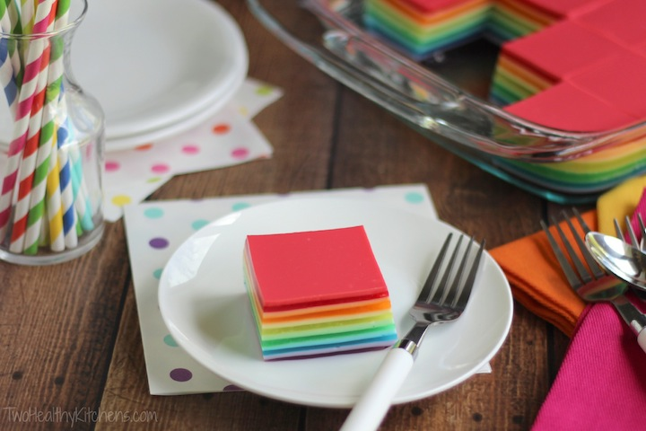 one square piece of this Jell-O Salad on a white plate, surrounded by colorful polka-dot napkins and striped party straws, and by the pan full of remaining Jell-O