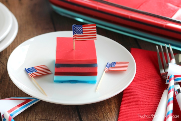 this recipe adapted to have patriotic, red-white-and-blue layers instead of rainbow layers, with a piece on a white plate with little flags on it and a red napkin nearby