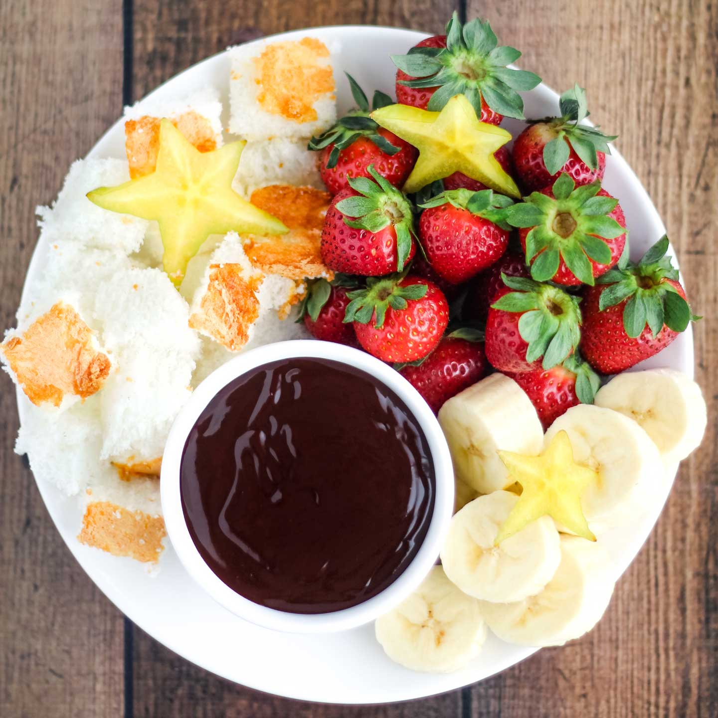 overhead of a fruit platter with strawberries, sliced bananas, chunks of angel food cake, and sliced star fruit, with a bowl of Chocolate Dip nestled in