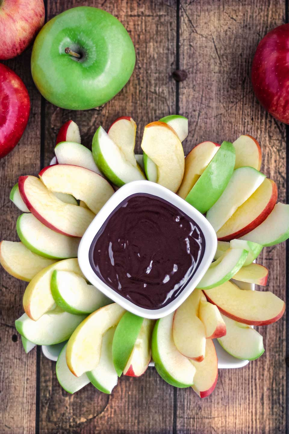 overhead of a platter of sliced red and green apples, with a square bowl of Chocolate Fruit Dip in the middle, and whole apples arranged alongside