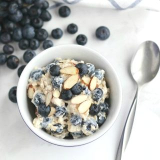 overhead of a bowl of these oats, ready to eat with a spoon alongside and blueberries cascading decoratively around the bowl