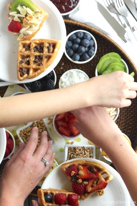 Overhead photo of several people's hand reaching across the scene, building their own waffle creations from little bowls of different toppings.