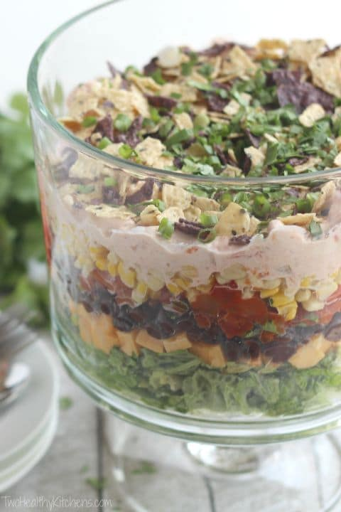 Tall glass trifle bowl filled with layered salad so you can see each layer