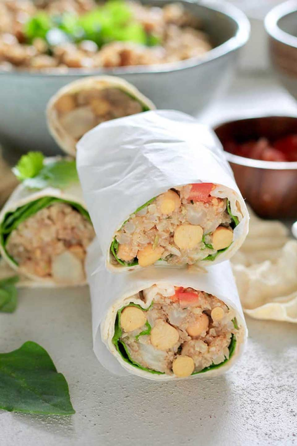 stack of two vegetarian wraps, cut open and wrapped in white deli paper