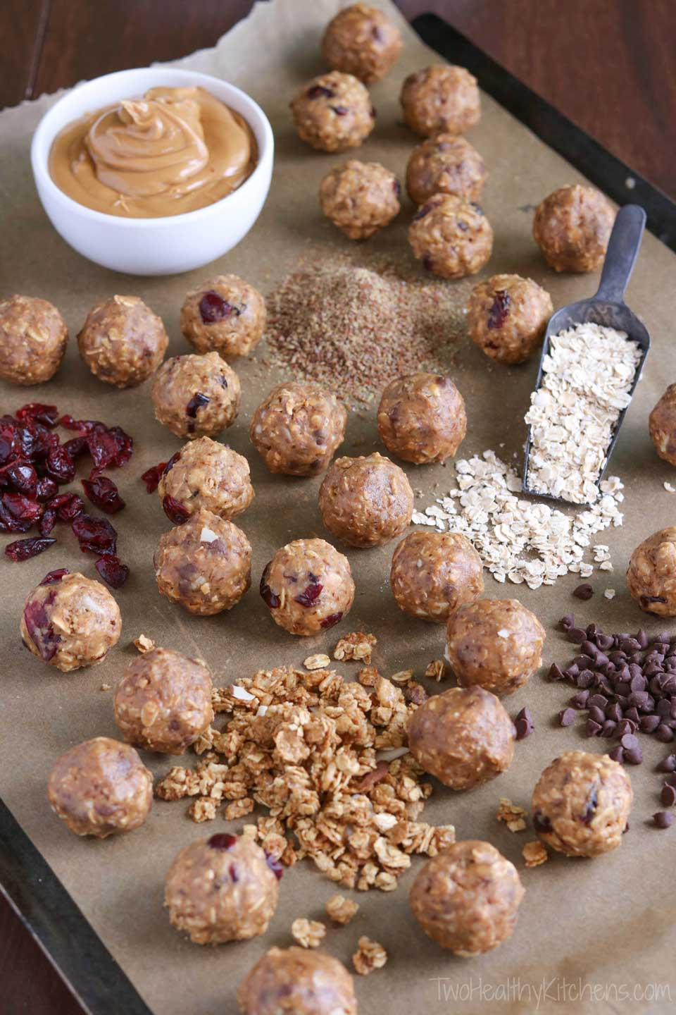 Freezable, no-bake Energy Balls with protein and whole grains! These Crunchy Granola Snack Bites will keep you satisfyingly full and power you through whatever the day might hold. A perfect healthy snack recipe, or a grab-and-go, make-ahead breakfast recipe! With peanut butter, oats, flax, and granola, plus dried fruit or chocolate chips - these energy bites are crunchy, chewy, and delicious! A healthy recipe with a few simple ingredients you probably have on hand! | www.TwoHealthyKitchens.com
