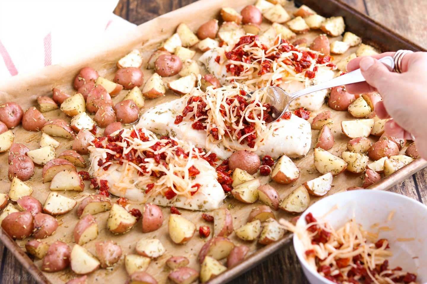 Incredibly delicious, with such easy cleanup! This sheet pan chicken dinner recipe features tender, juicy chicken breasts and perfectly baked redskin potatoes. All accented with rosemary, crowned with a scrumptious topping of sun-dried tomatoes and Italian cheeses, then finished with a honey-balsamic drizzle! This sheet pan supper recipe takes chicken and potatoes to a whole new level! Easy enough for weeknight dinners (make-ahead tips!), special enough for company! | www.TwoHealthyKitchens.com
