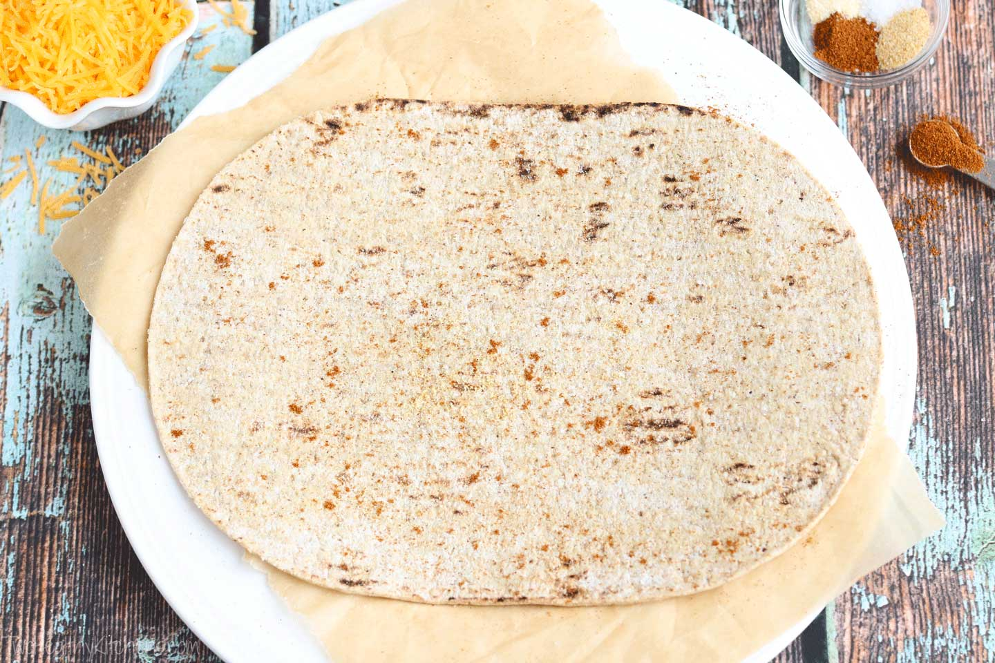 To make each DIY Tacone, start by sprinkling each flatbread with Mexican spices.