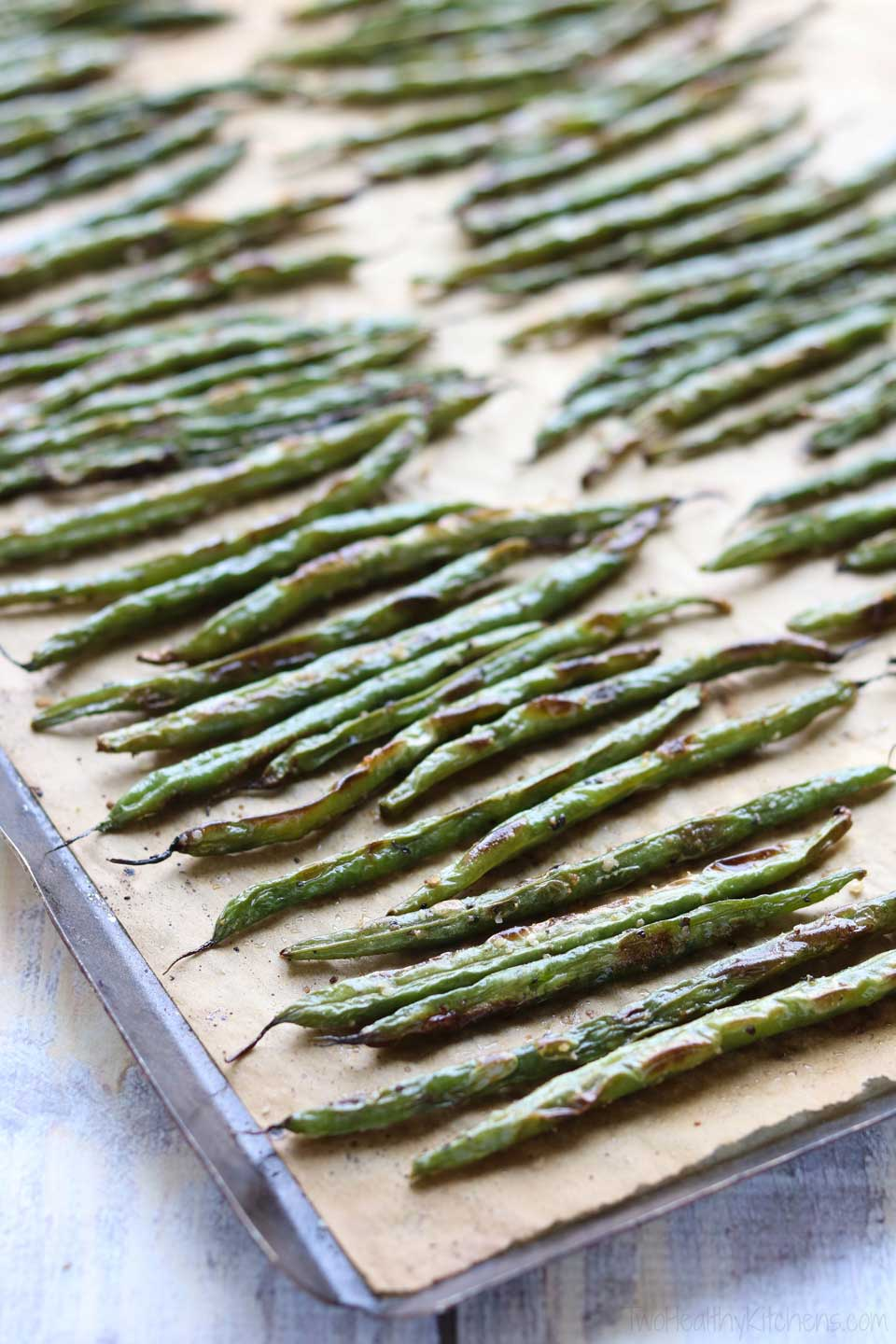 How do you roast green beans so they're perfectly blistered and delicious? One key is making sure that they have plenty of room on the baking sheet. Don't pile them up, or they'll tend to steam more than roast!