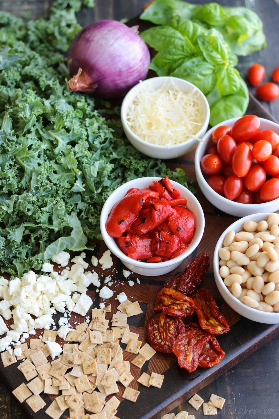 Besides nutritious kale, this salad features two kinds of tomatoes and two kinds of cheese, plus roasted red peppers, fresh basil, red onions, cannellini beans, and a wonderfully simple honey-balsamic dressing!