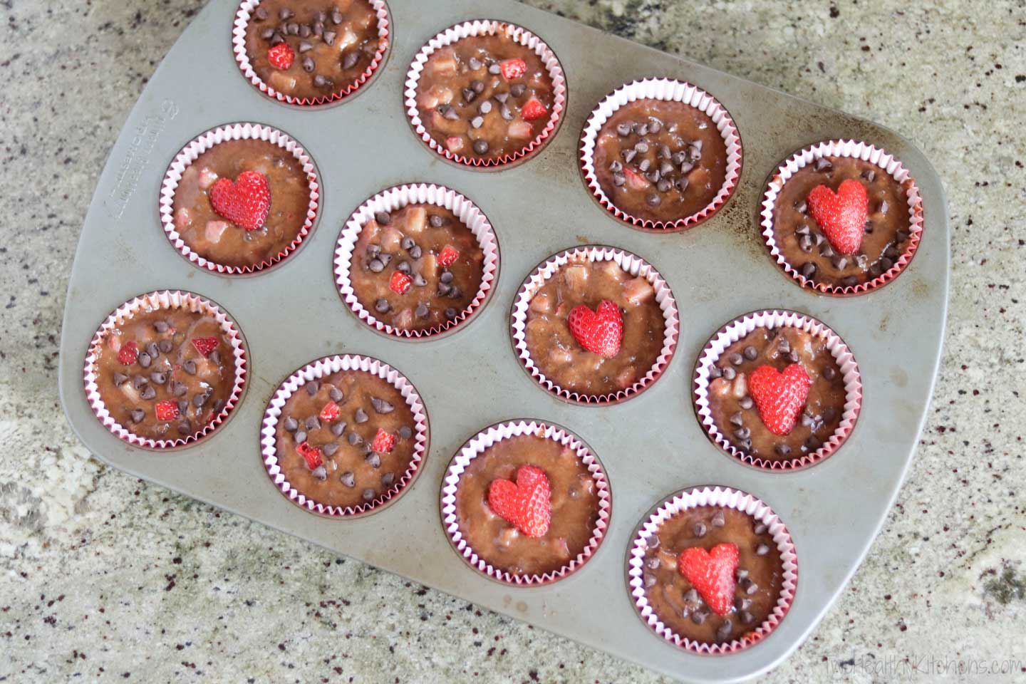 a pan of muffins waiting to be baked, with heart-shaped strawberries decorating the tops