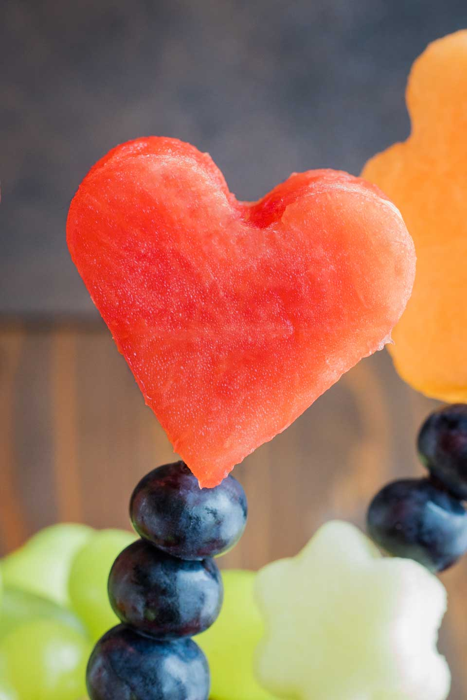 closeup of a heart cut out of watermelon, skewered on a kabob with blueberries and other fruit