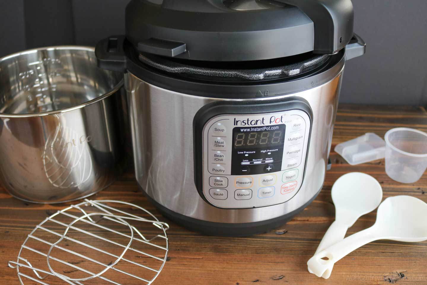 Instant Pot with all the things an Instant Pot comes with - stainless steel inner pot, steaming rack, condensation collector, rice paddle, soup spoon and measuring cup