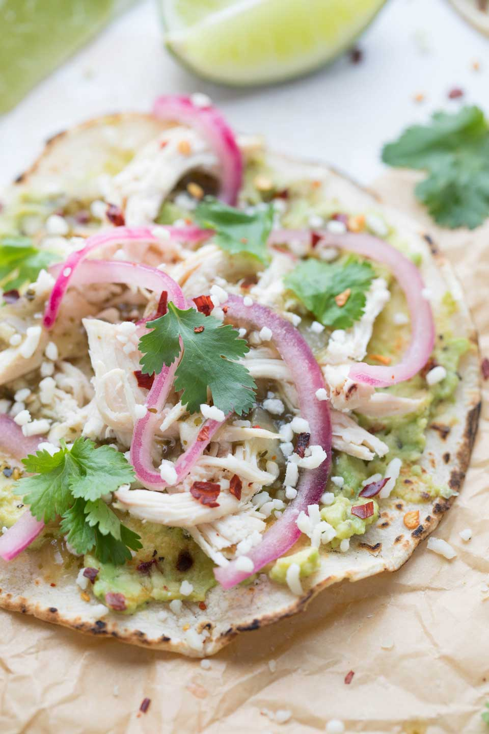 """Featuring a yummy """"smashed avocado"""" guacamole spread and quick pickled onions, these chicken tacos have lots of unique flavors – truly something special! Definitely a recipe to try for your next Taco Tuesday dinner, or even for a tailgating make-your-own taco bar … and of course, for Cinco de Mayo!"""