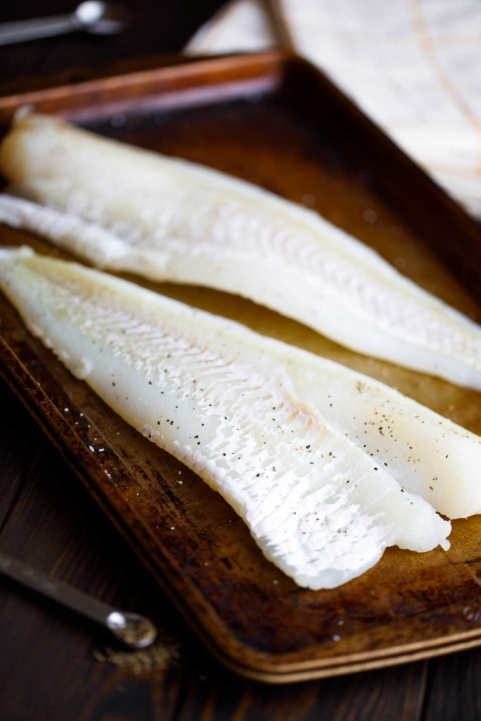 Photo of two cod fillets on baking tray, sprinkled with kosher salt and black pepper.