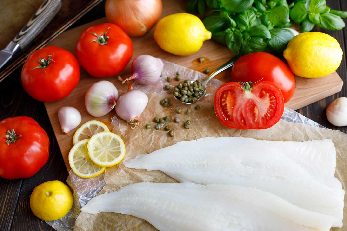Ingredients needed to make this broiled fish recipe - cod fillets, fresh tomatoes, lemons, shallot, onion, capers, and basil.