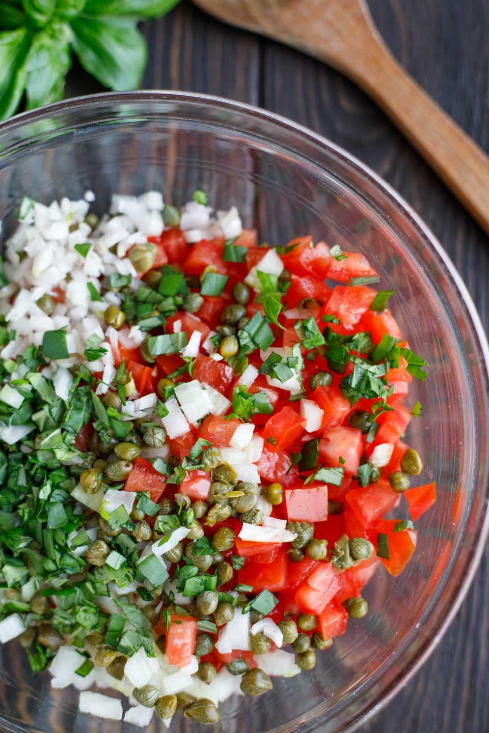 Glass bowl filled with ingredients for the topping in this broiled fish recipe - capers and chopped fresh tomatoes, onions, shallots, and basil.