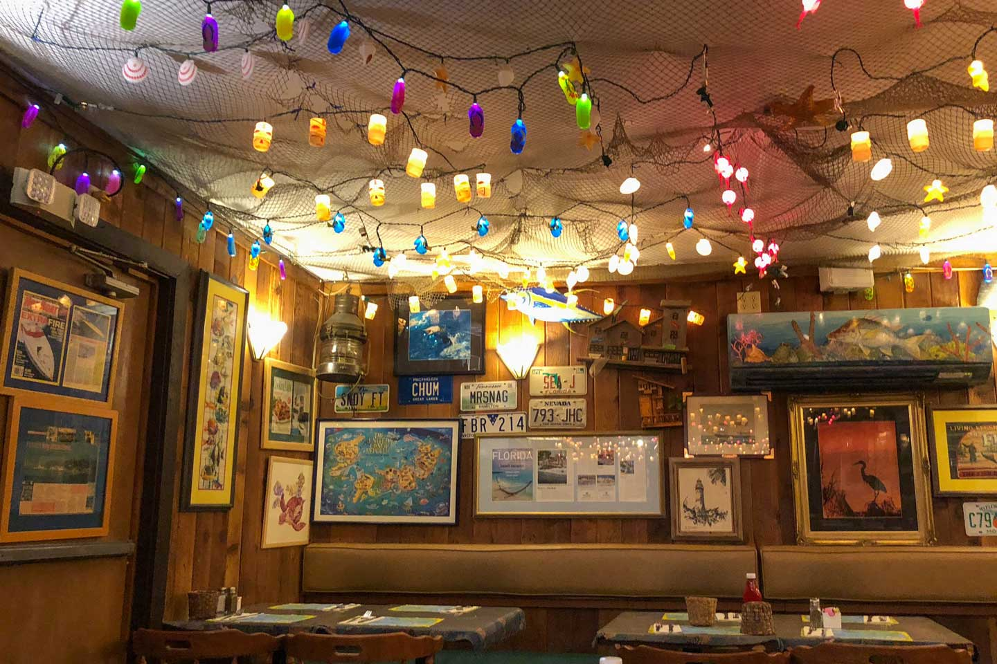 Interior of The Fish House restaurant in Key Largo, Florida with plastic party lights strung from the ceiling.