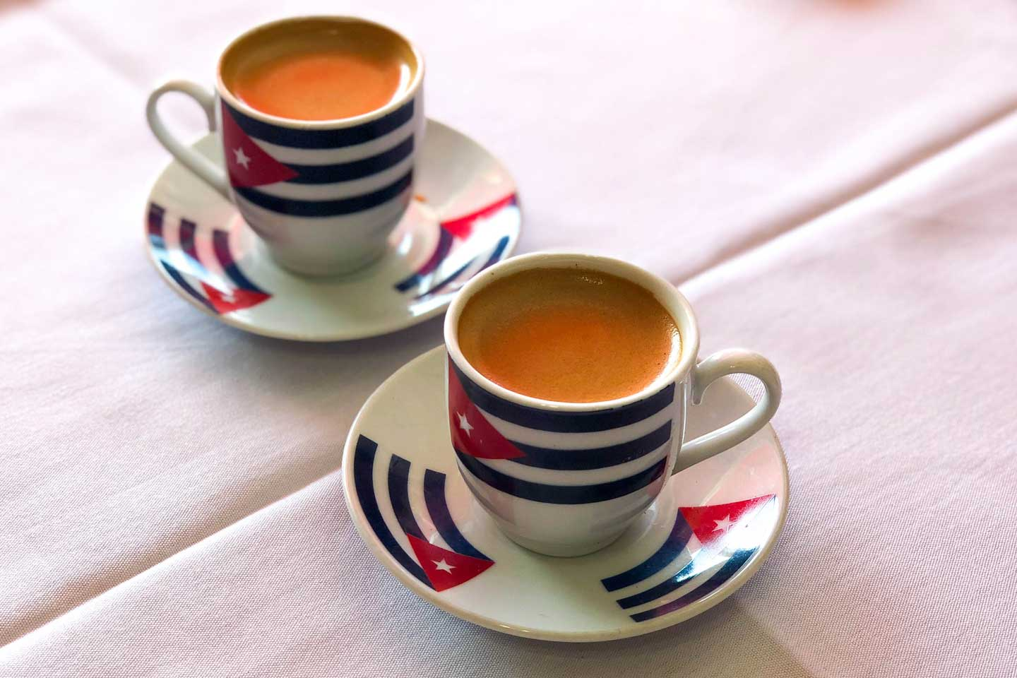 Two small cups of Cuban Coffee on a white table cloth at Denny's Latin Cafe in Key Largo, Florida.