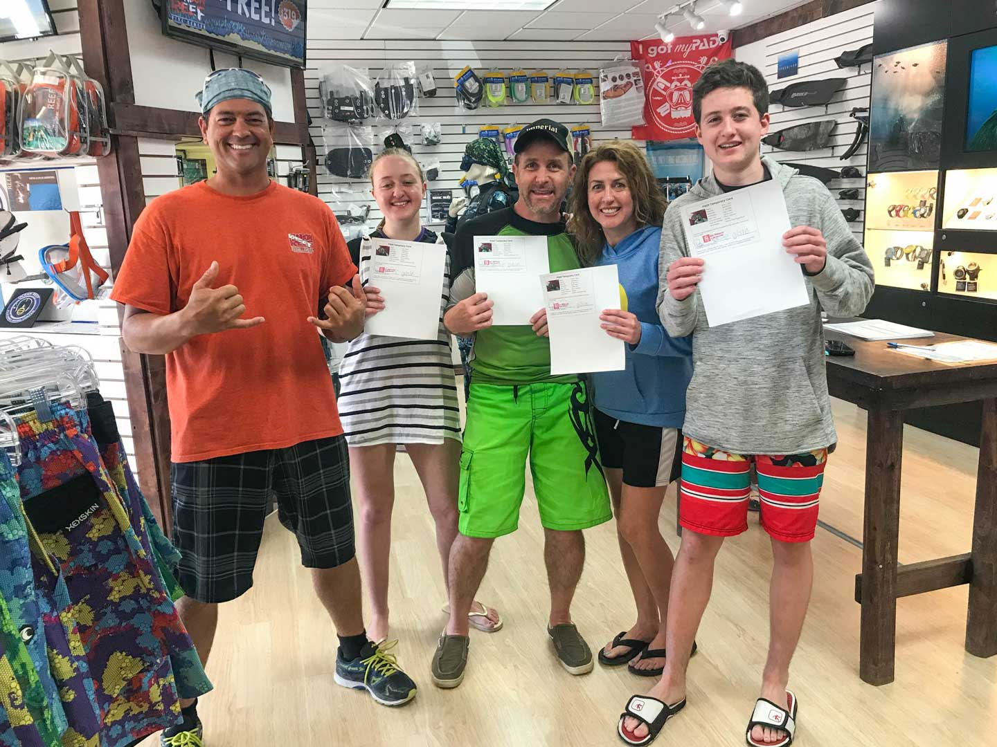 Our family, along with our dive instructor, Rex - posed together inside the dive shop and holding our dive certification papers in victory!