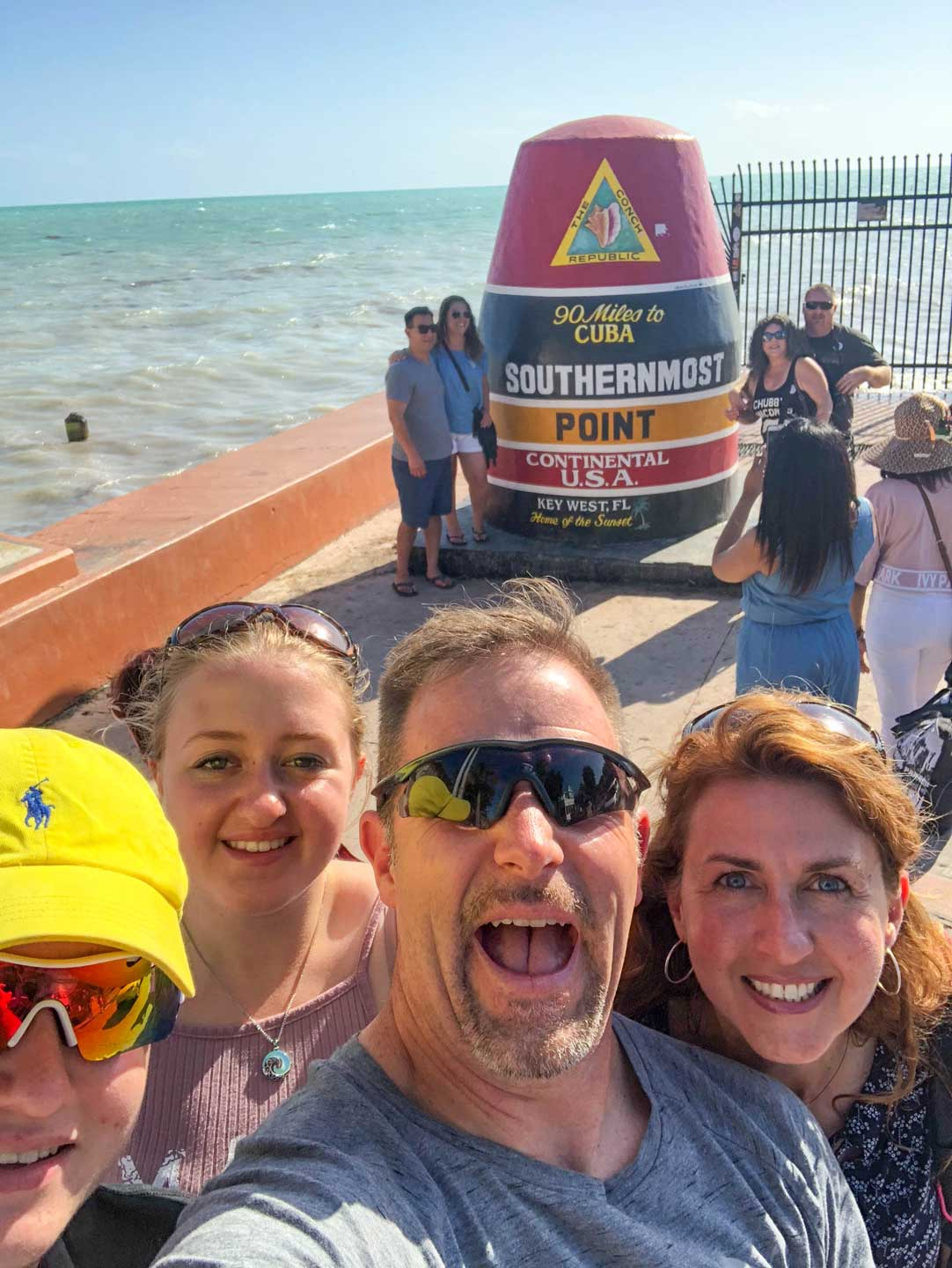 Family selfie in Key West, in front of the marker for the Southernmost Point in the Continental US.