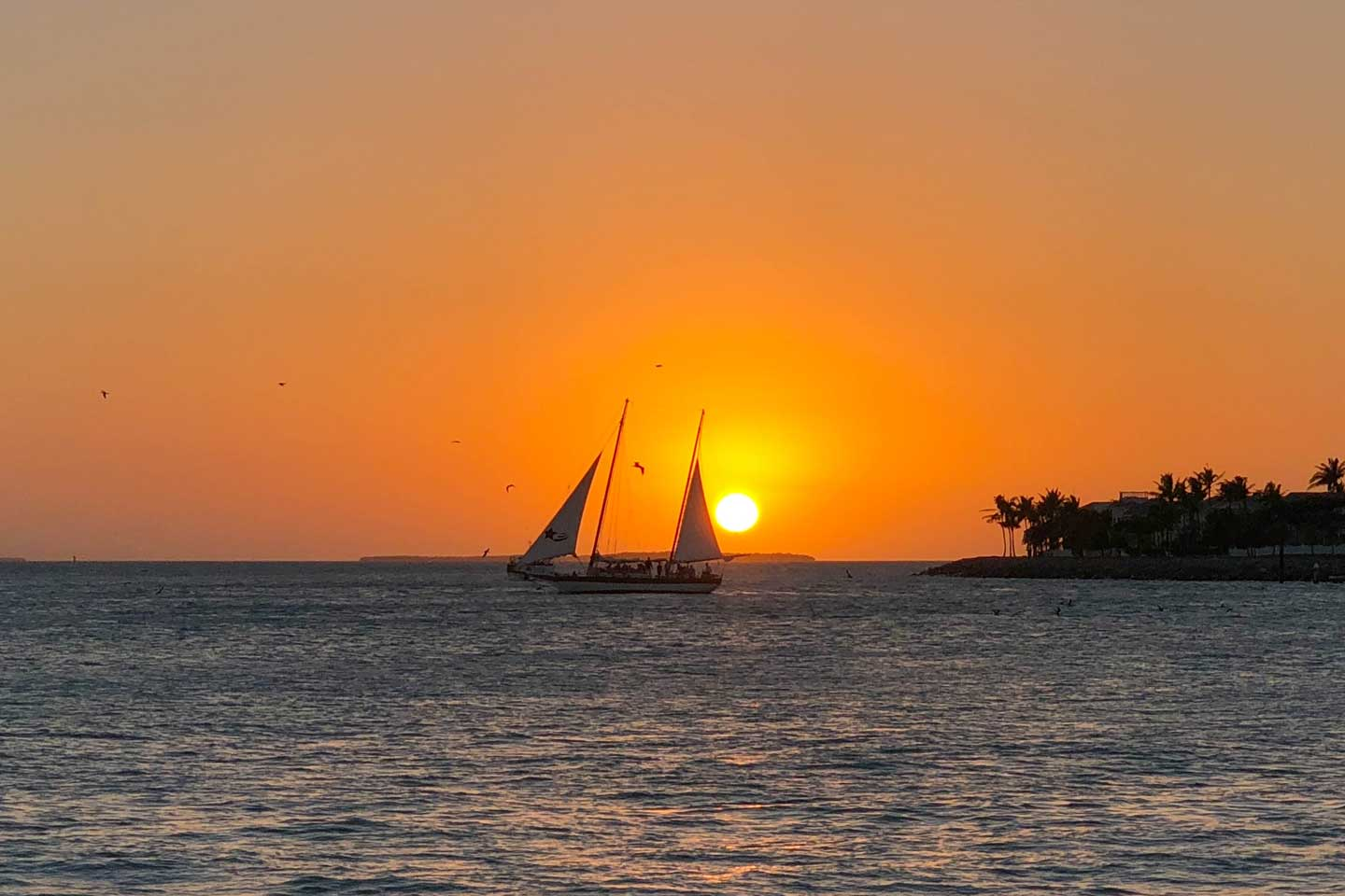 Sunset in Key West with the ocean in the foreground and a boat passing by the orange sun just before it sets.