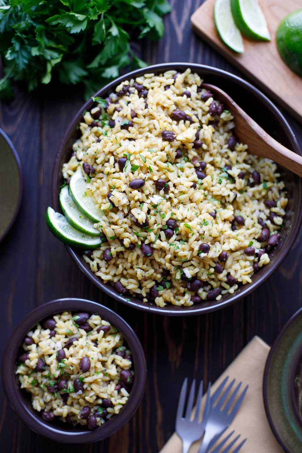 Overhead, flat lay photo of this Easy Beans and Rice recipe in a large serving bowl, along with a small dishful, some forks, lime wedges and a bunch of parsley