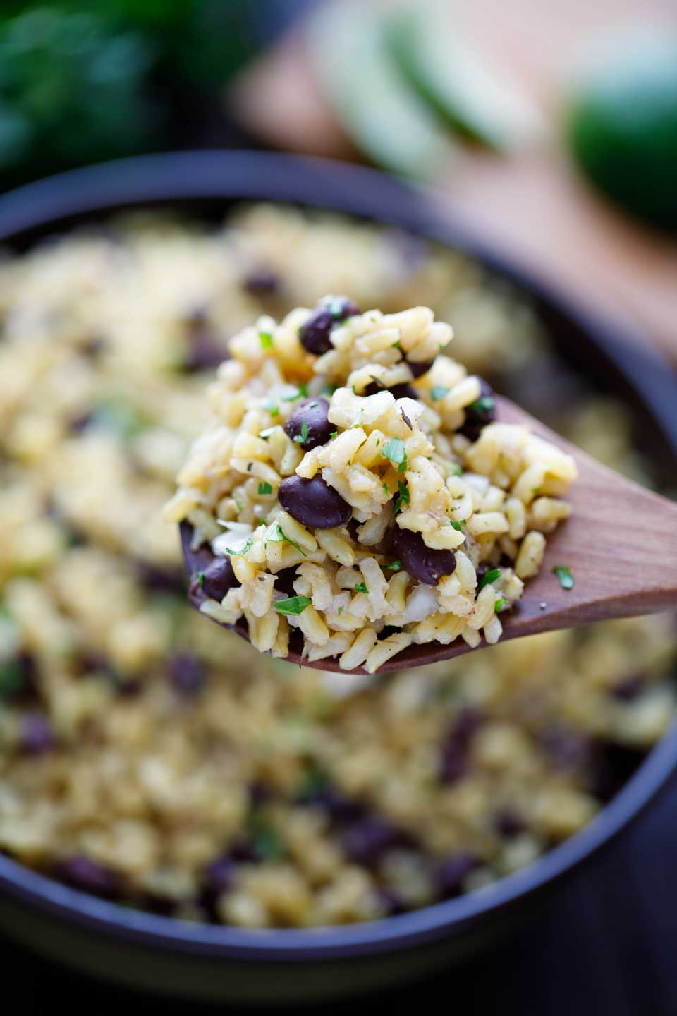 Wooden spoon piled with a scoop of this Easy Rice and Beans recipe, with the serving bowl in the background