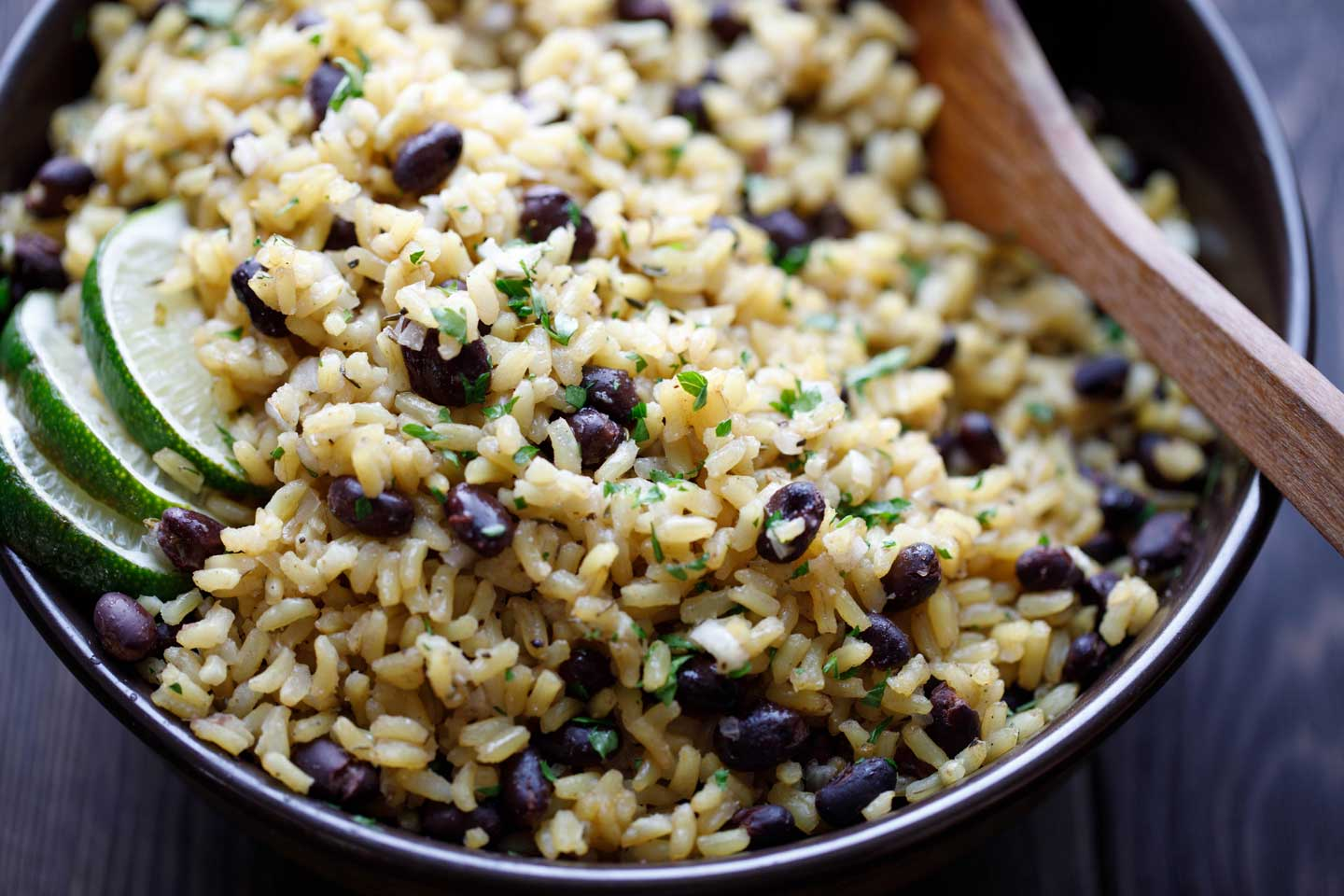 Closeup of serving bowl filled with this Rice and Beans recipe, parsley sprinkled on top and lime wedges tucked at the side
