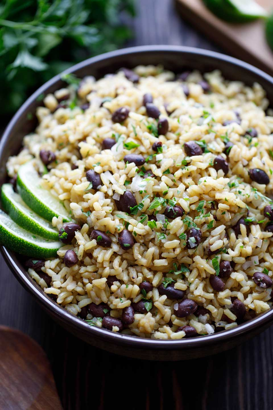 Serving bowl filled with this brown rice and black beans side dish, with lime wedges and parsley in the background