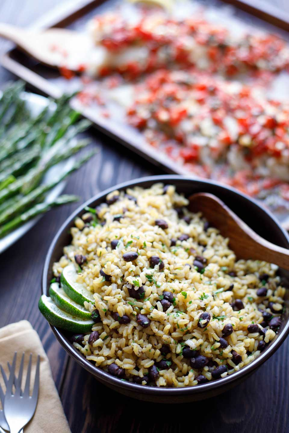 Serving bowl filled with Easy Black Beans and Rice in the foreground, with asparagus and a Matecumbe Fish in the background