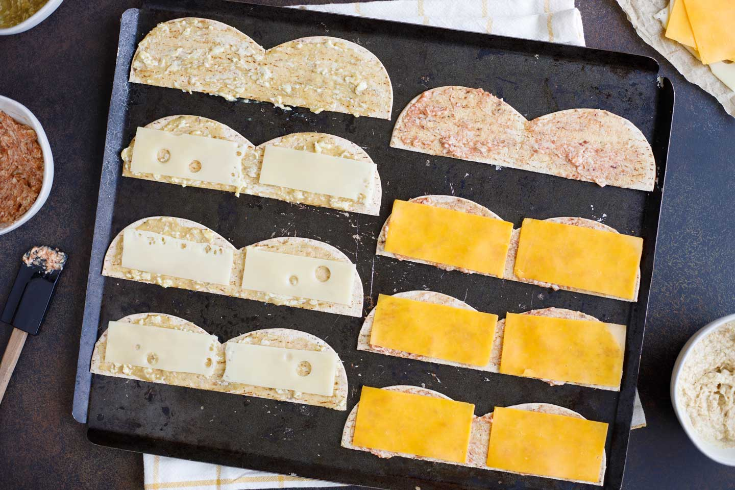 Halved flatbreads laid out and topped with sandwich spreads and cheeses, surrounded by more cheese and spreads