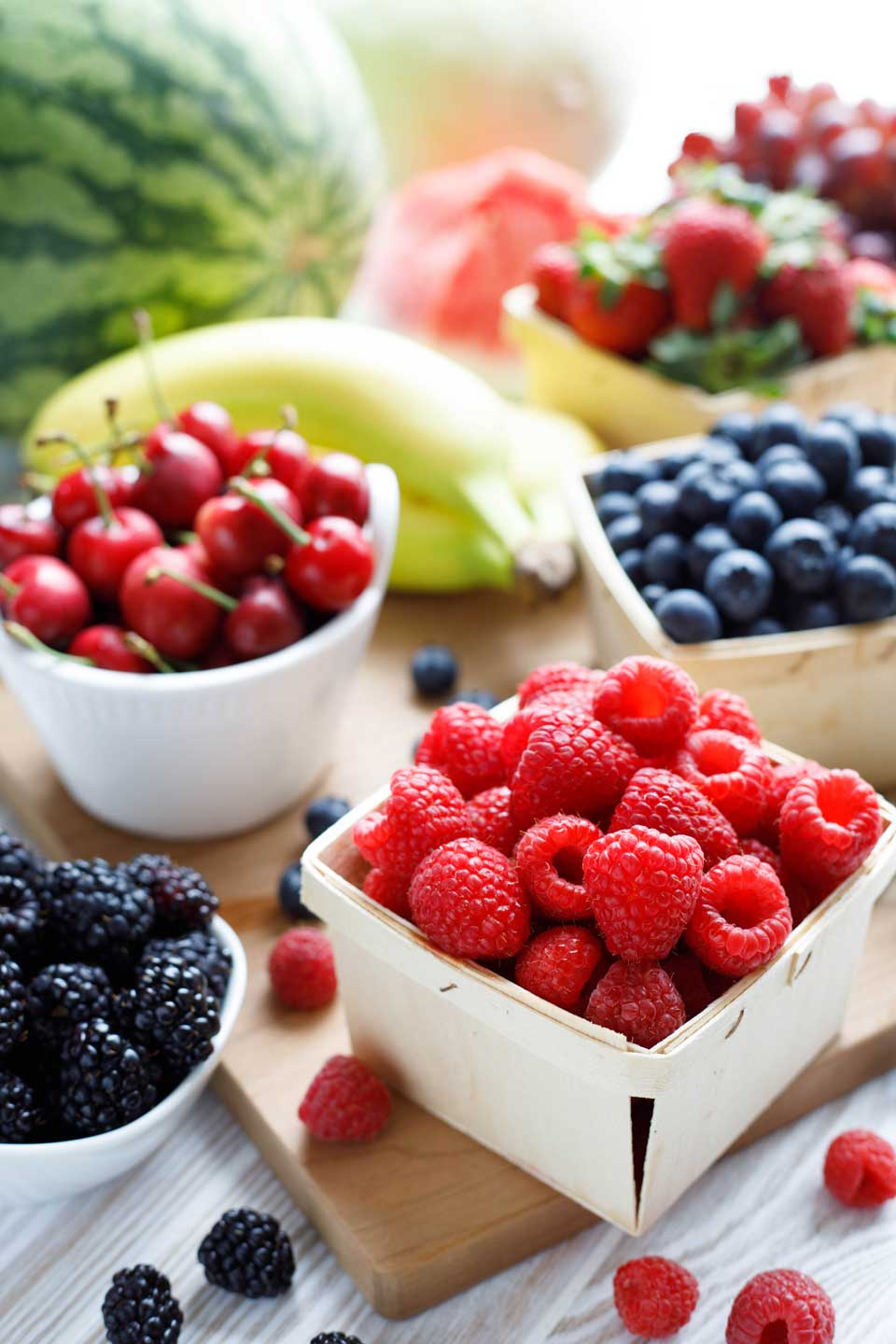 Fresh fruits arranged in little baskets and bowls, including raspberries, blueberries, blackberries, cherries and strawberries