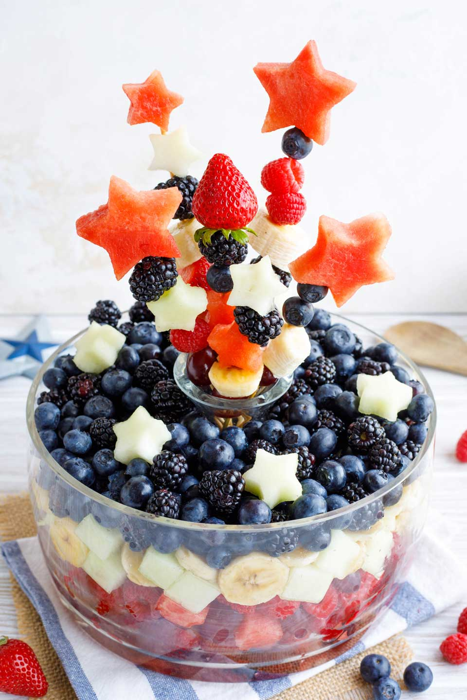 Layered red, white and blue fruit salad - turned into a centerpiece by adding fruit kabobs to a vase at the center