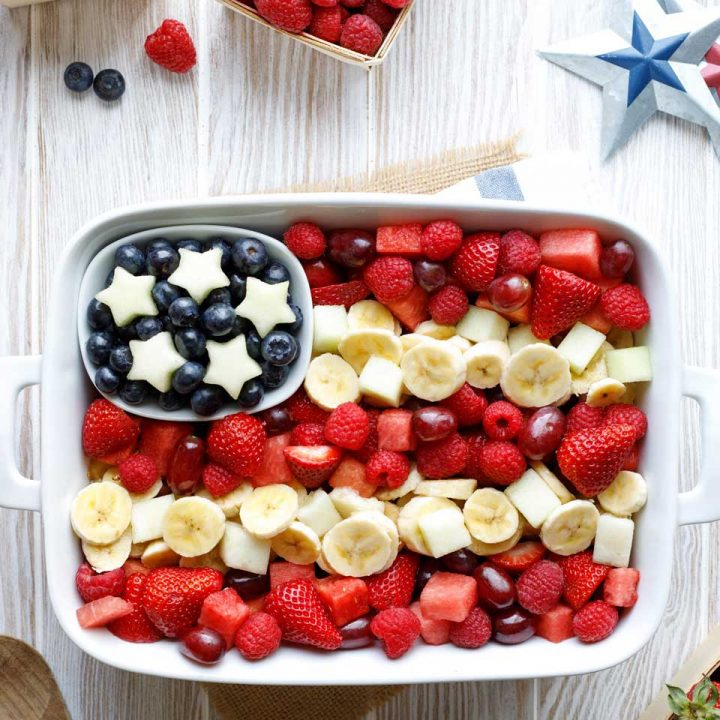 overhead of fruit salad arranged in a white dish to look like an American flag