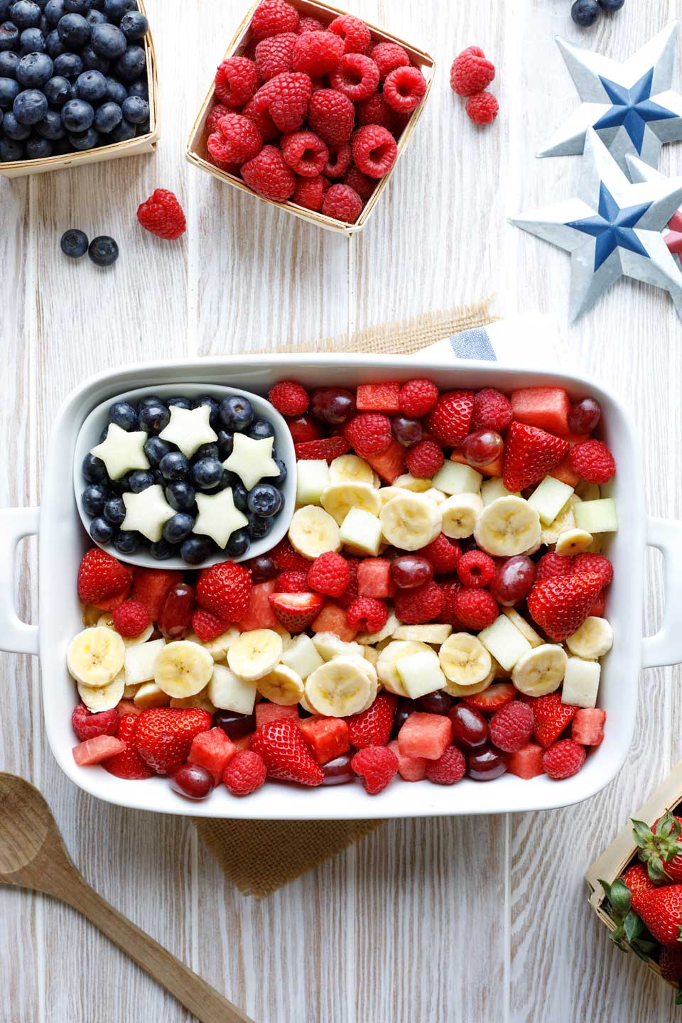 Flag fruit salad in a rectangular pan, with white melon stars on the field of blue