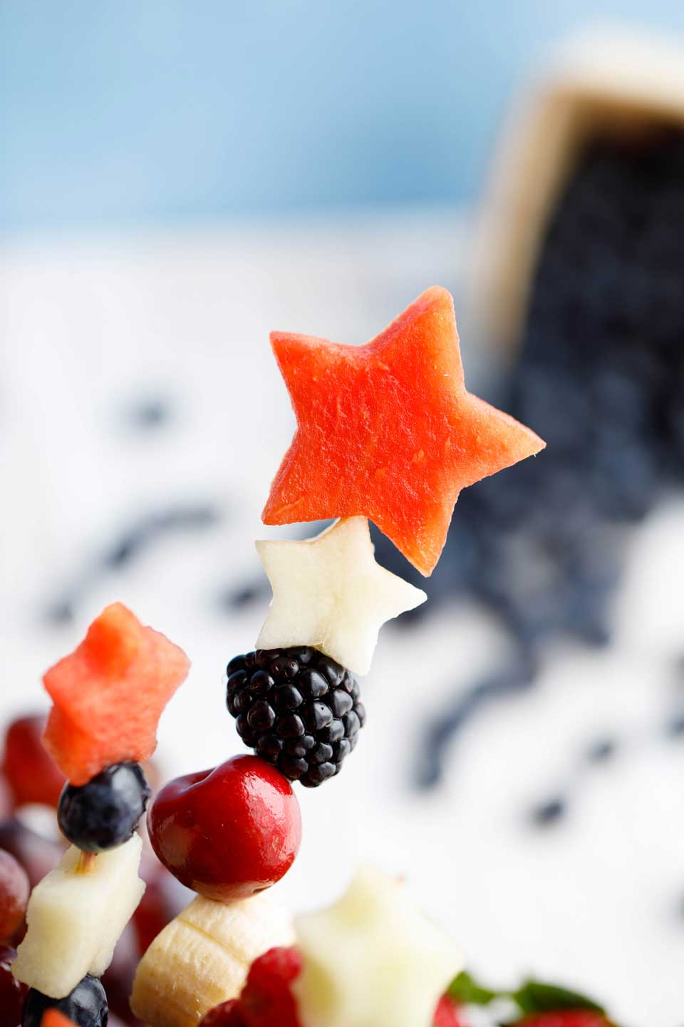 Closeup of two star cutouts and other fruit on a fruit kabob