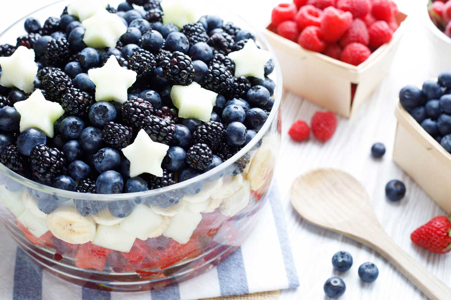 Layered fruit salad topped with white melon stars, surrounded by red and blue fruits and wooden spoon